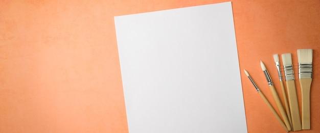Czysty biały arkusz i pędzle na teksturowanym tle z miejscem do kopiowania. układ, makieta miejsca na tekst i rysunek.