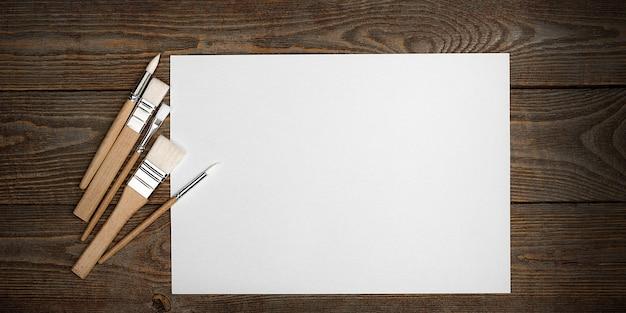 Czysty biały arkusz i pędzle na tle z teksturą drewna z miejscem do skopiowania.