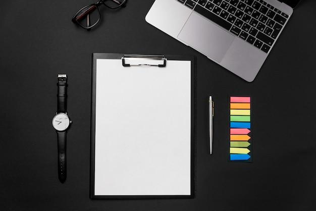 Czysty biały arkusz papieru z bezpłatną przestrzenią do kopiowania, laptopem, zegarkiem i długopisem na czarnym tle.