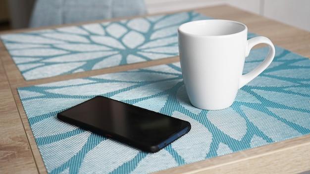 Czysty biały kubek z uchwytem i smartfonem na niebieskim stole