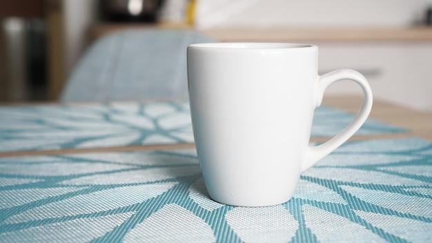 Czysty biały kubek z uchwytem stoi na niebieskim stoliku z tyłu