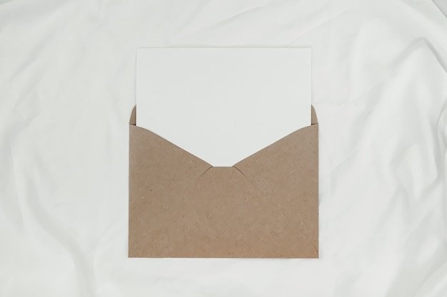Czysty biały papier umieszcza się na otwartej brązowej kopercie papierowej na białej szmatce. widok z góry koperty z papieru craft na białym tle.