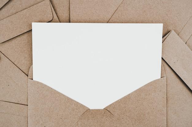 Czysty biały papier umieszczony na otwartej brązowej kopercie papierowej. makieta poziomej pustej karty z pozdrowieniami