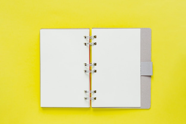 Czysty notes z celami i rozwiązaniami w recyklingu okładki papieru. makieta do swojego projektu. ślimakowata nutowa książka na żółtym tle.