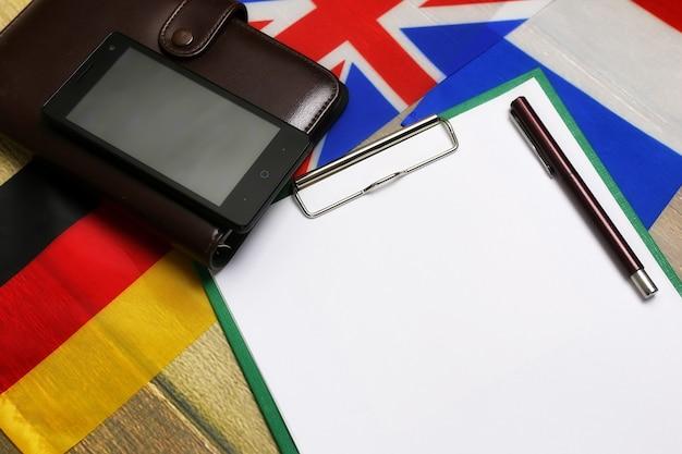 Czysty papier na drewnianym biurku z teksturą ze słuchawkami telefonu komórkowego i flagami