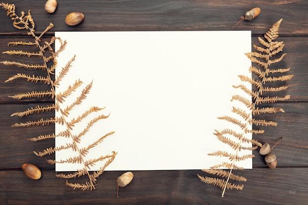 Czysty papier na drewnianym stole i jesiennej dekoracji