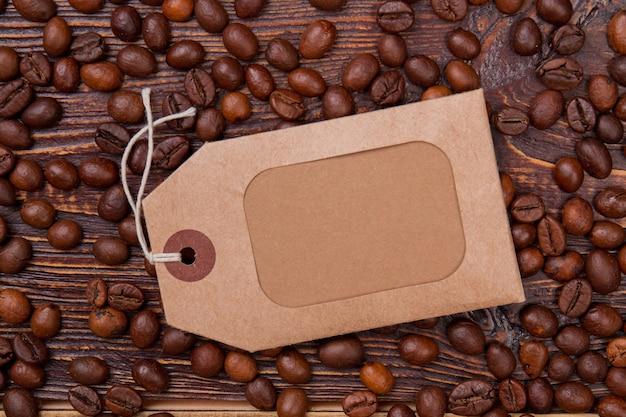 Czysty papierowy znacznik na drewnie z ziarnami kawy