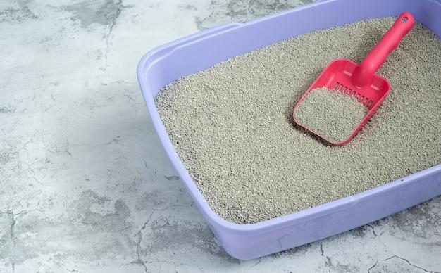 Czysty piasek w żwirku i szufelce dla kota, higiena zwierząt