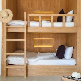 Czysty pokój z drewnianymi łóżkami piętrowymi.
