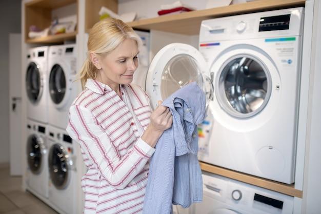 Czysty ręcznik. blondynka w pasiastej koszuli siedzi na pralce i trzymając ręcznik