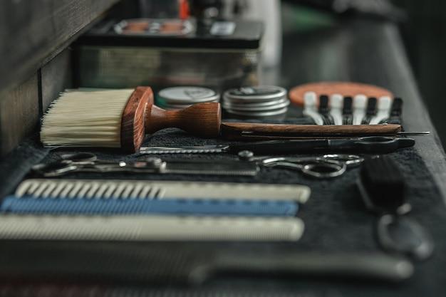 Czysty sprzęt fryzjerski umieszczony na czarnym ręczniku na ladzie fryzjerskiej