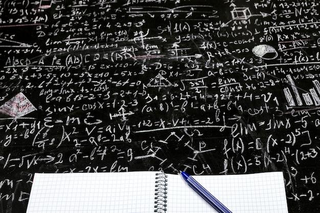Czysty zeszyt ucznia z tablicą z długopisem z przykładami i wzorami