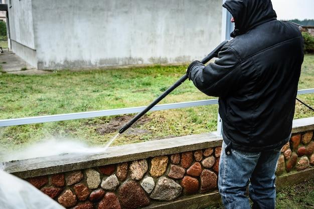 Czyszczenie brudnego ogrodzenia kamiennego za pomocą myjki wysokociśnieniowej