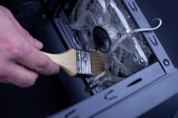 Czyszczenie brudnego wentylatora procesora komputera stacjonarnego z kurzu specjalną szczoteczką z bliska