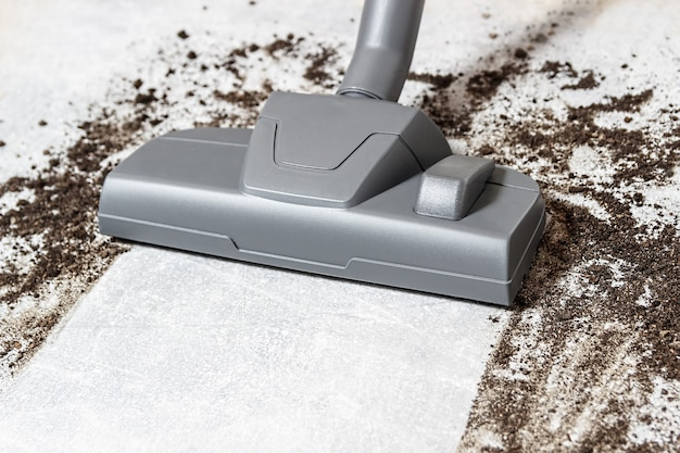 Czyszczenie brudnej podłogi odkurzaczem w salonie