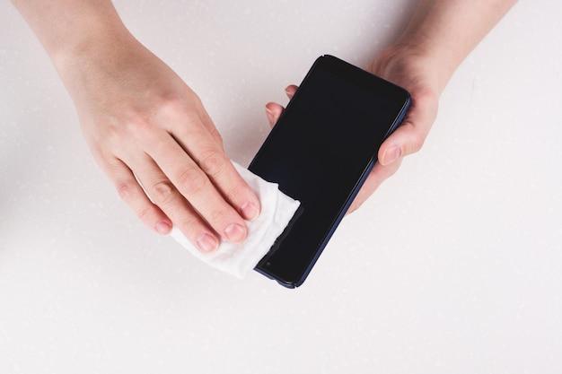 Czyszczenie ekranu telefonu komórkowego żelem dezynfekującym. prewencyjna kwarantanna narzędzi w przypadku koronawirusa