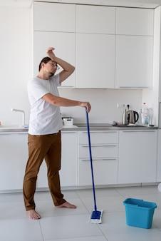 Czyszczenie i dezynfekcja. młody człowiek w białej koszuli sprzątanie kuchni z miotłą