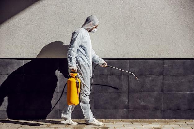 Czyszczenie i dezynfekcja na zewnątrz wokół budynków, epidemia covid-19. sesyjne zespoły do dezynfekcji. zapobieganie infekcjom i kontrola epidemii. kombinezon i maska.