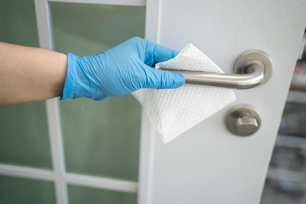 Czyszczenie klamki do drzwi szmatką i chusteczką w biurze i domu w celu ochrony koronawirusa covid 19 19
