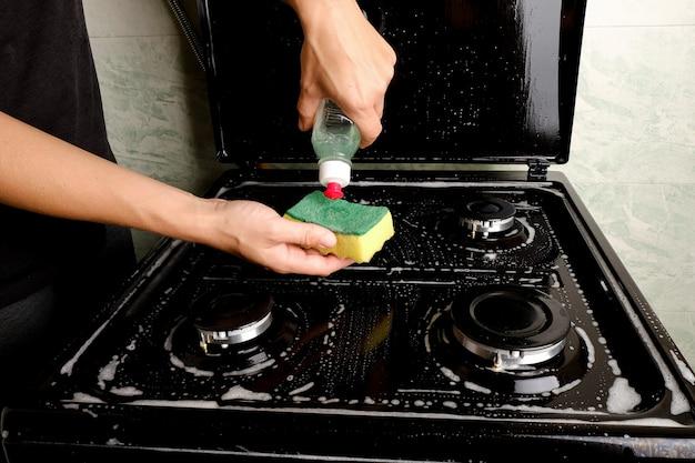 Czyszczenie kuchenki gazowej w kuchni detergentem i gąbką. sprzęt gospodarstwa domowego do gotowania. czyszczenie powierzchni.