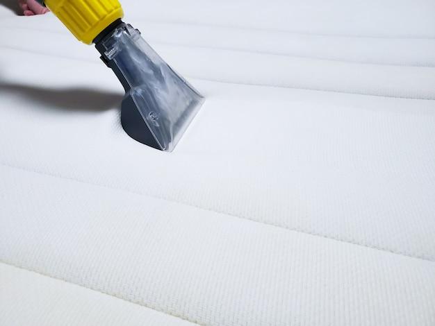 Czyszczenie na sucho białego materaca na łóżku. czyszczenie na mokro.