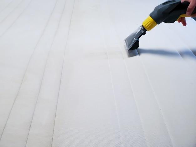 Czyszczenie na sucho materaca na łóżku profesjonalnym wyposażeniem.