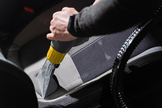 Czyszczenie na sucho w salonie samochodowym za pomocą odkurzacza. profesjonalne użycie odkurzacza parowego do usuwania plam