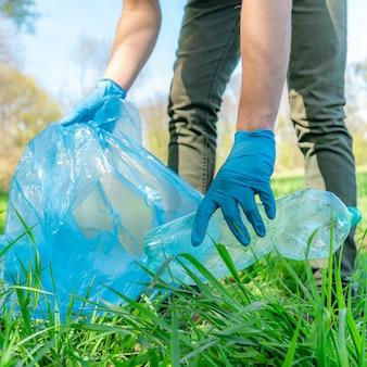 Czyszczenie natury poprzez zbieranie odpadów z tworzyw sztucznych, plastikowe butelki z napojem powodują katastrofę ekologiczną