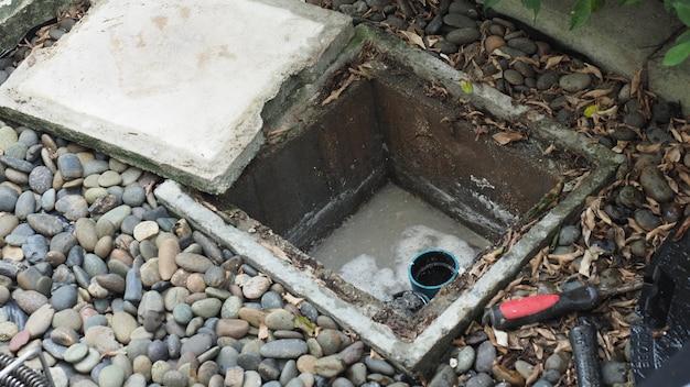 Czyszczenie odpływów. hydraulik naprawia zatkany łapacz tłuszczu z maszyną ślimakową. konserwacja kanalizacji i odtłuszczacza przez profesjonalnego hydraulika. używanie węża ślimakowego do naprawy i udrażniania odpływu.