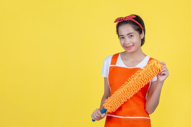 Czyszczenie . piękna kobieta z urządzeniem czyszczącym na żółtym.