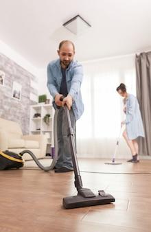 Czyszczenie podłogi odkurzaczem używanym przez męża