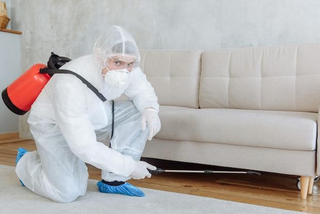Czyszczenie. pracownicy w kombinezonach ochronnych dezynfekują swoje mieszkanie chemikaliami, kopiują przestrzeń. koncepcja pandemicznej dezynfekcji koronawirusa lub covid-19