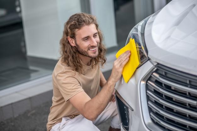 Czyszczenie samochodu. młody mężczyzna siedzi i czyści reflektory samochodowe