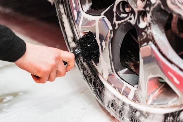 Czyszczenie samochodu odlewanych srebrnych felg samochodowych za pomocą szczotki
