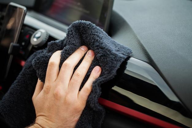 Czyszczenie samochodu. ręka z ściereczką z mikrofibry do czyszczenia wnętrza samochodu