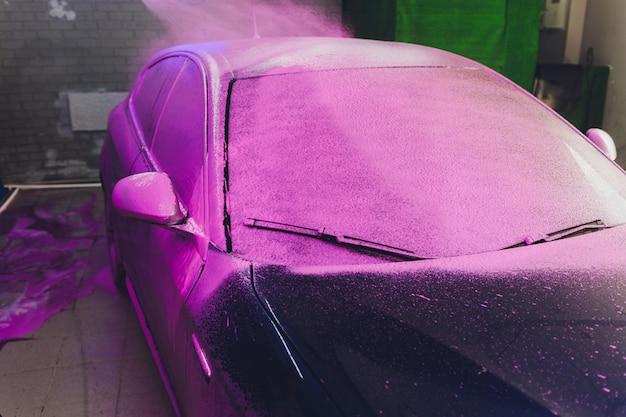 Czyszczenie samochodu z bliska za pomocą wody pod wysokim ciśnieniem, myjka wysokociśnieniowa w procesie mycia samochodu. różowa pianka