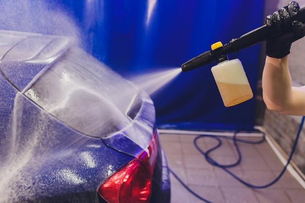 Czyszczenie samochodu z bliska za pomocą wody pod wysokim ciśnieniem, myjka wysokociśnieniowa w procesie mycia samochodu.