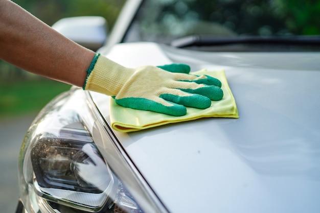 Czyszczenie samochodu z zieloną tkaniną z mikrofibry na zewnątrz w wakacje.