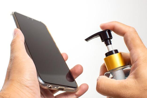 Czyszczenie smartfona środkiem dezynfekującym w żelu alkoholowym w celu zapobiegania infekcji,