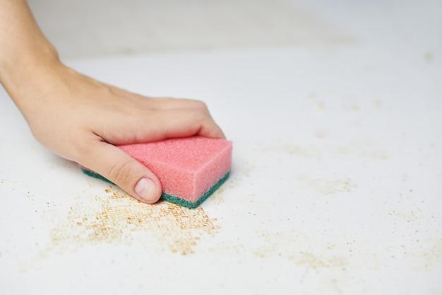 Czyszczenie stołu kuchennego. różowa gąbka w kobiecej dłoni usuwa brud, okruchy chleba i resztki. prace domowe
