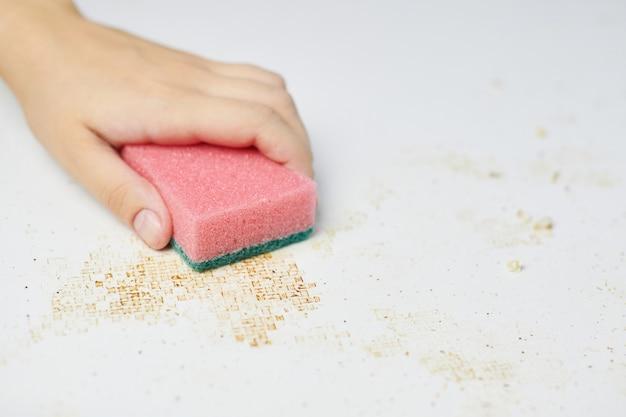 Czyszczenie stołu kuchennego różową gąbką