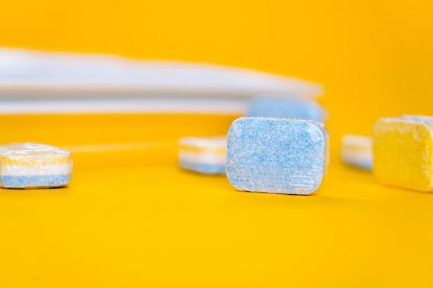 Czyszczenie tabletek do zmywarki białą płytką na żółto.