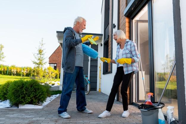 Czyszczenie terytorium. nowoczesna śmiejąca się babcia i dziadek bawią się podczas sprzątania terenu w pobliżu letniego domu