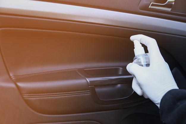 Czyszczenie wnętrza samochodu i spryskiwanie płynem dezynfekcyjnym. dezynfekcja kierownicy i uchwytów samochodu. koronawirus, ochrona covid-19. dezynfekcja pojazdu wewnątrz,