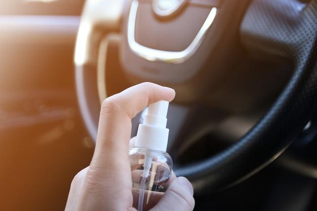 Czyszczenie wnętrza samochodu płynem do dezynfekcji. dezynfekcja kierownicy i uchwytów samochodu. koronawirus, ochrona covid-19 dezynfekcja pojazdu wewnątrz