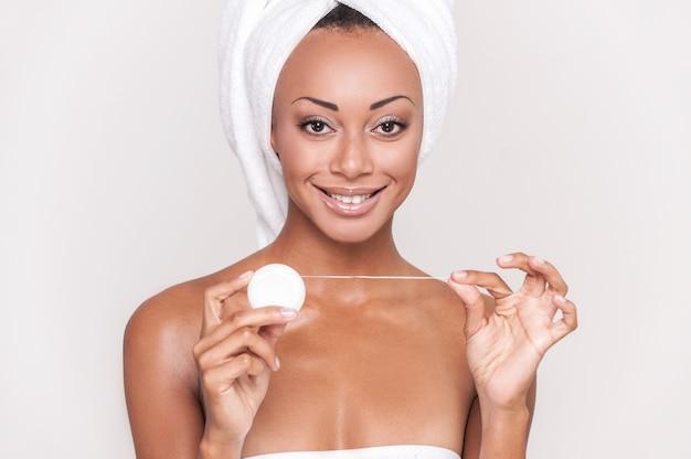 Czyszczenie zębów. piękna młoda afroamerykańska kobieta trzyma nić dentystyczną i uśmiecha się do kamery, podczas gdy izolowany na szarym tle