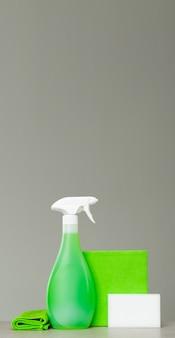 Czyszczenie zielonej butelki z rozpylaczem z plastikowym dozownikiem, gąbką i ściereczką do kurzu.