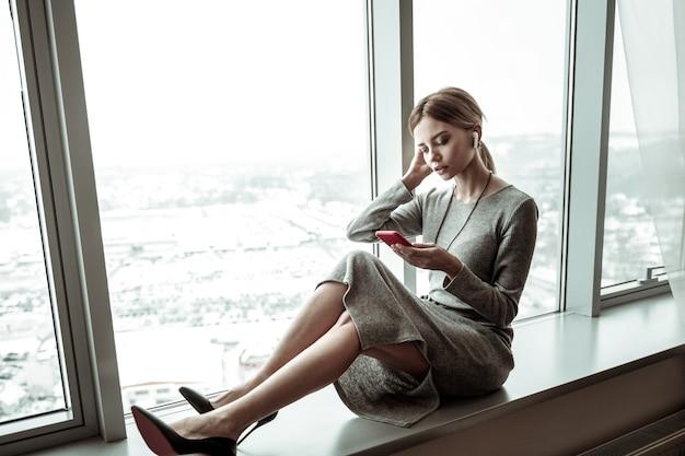 Czytanie aktualności. piękna stylowa kobieta siedzi na parapecie podczas czytania aktualności na smartfonie