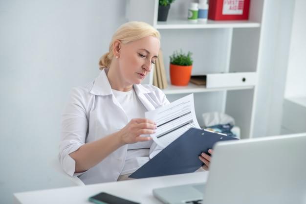Czytanie. blondynka w średnim wieku lekarz siedzący przy biurku i patrząc poważnie