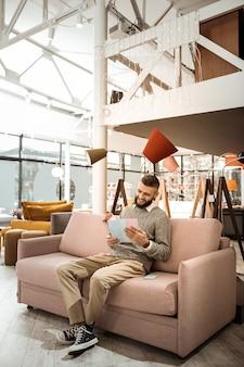 Czytanie broszury. śmiejący się brodaty mężczyzna czeka na swoją żonę na wygodnej sofie i czasopiśmie obserwacyjnym